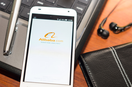 alibaba: QUITO, ECUADOR - AUGUST 3, 2015: White smartphone closeup lying on laptop corner with Alibaba website screen visible, eaplugs mouse and pen blurry background, business communication concept.