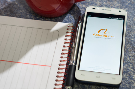 alibaba: QUITO, ECUADOR - AUGUST 3, 2015: White smartphone lying on table with Alibaba website screen open next to a pen, notepad and coffee mug, business communication concept.