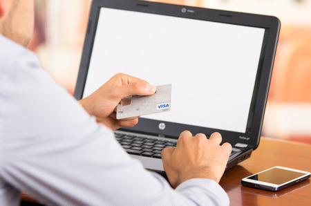 visa credit card: QUITO, ECUADOR - AUGUST 3, 2015: Closeup of man sitting by desk with laptop computer holding up Visa credit card in front of screen as in shopping online. Editorial