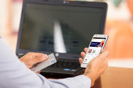 tarjeta visa: QUITO, ECUADOR - AGOSTO 3, 2015: Primer plano de jóvenes sirve las manos que sostiene teléfono inteligente con el sitio web de Alibaba visible, tarjeta Visa en el otro lado con el ordenador portátil sentado en el escritorio.