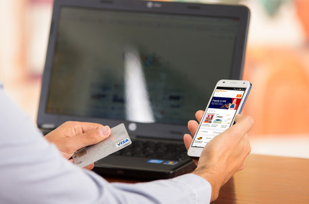 alibaba: QUITO, ECUADOR - AUGUST 3, 2015: Closeup of young mans hands holding smartphone up with Alibaba website visible, Visa card in other hand with laptop computer sitting on desk.