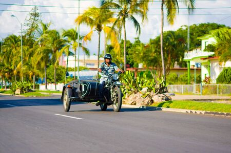 enfield: CIENFUEGOS, CUBA - SEPTEMBER 12, 2015: Classic motorcycle with sidecar are still in use and old timers have become an iconic view
