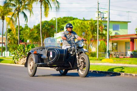 sidecar: CIENFUEGOS, CUBA - SEPTEMBER 12, 2015: Classic motorcycle with sidecar are still in use and old timers have become an iconic view
