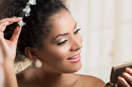 skin color: Closeup portrait of beautiful hispanic brunette young woman with curly hair wearing a floral hairband Stock Photo