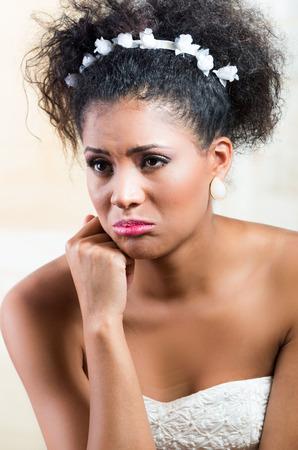inconsolable: Closeup portrait of beautiful exotic emotional bride looking sad