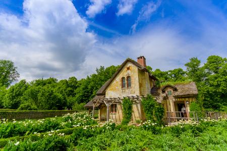 PARIS, FRANCE - JUNE1, 2015: Tourists visiting the Hameau de la Reine, The Queen's Hamlet is a rustic retreat in Versailles, Paris, France