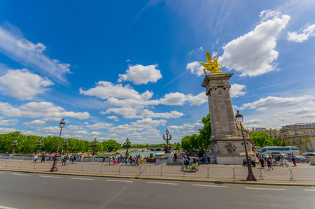 parisian scene: PARIS, FRANCE - JUNE 1, 2015: Beautiful parisian scene with Seine river behind a bridge