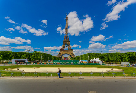 big screen: PARIS, FRANCE - JUNE 1, 2015: Beautiful summer view of the Eiffel Towel  with a big screen showing the Roland Garros French Open to tourists