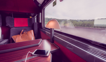 headrest: Cell phone charging in window seat in a modern comfortable train