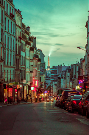 parisian scene: PARIS, FRANCE - JUNE 1, 2015: Beautiful and colorful evening parisian city street scene with Eiffel Tower in the background Editorial