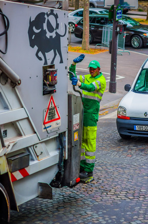 PARIS, FRANCE - JUNE 1, 2015: Garbage collector standing on garbage truck cleaning the streets in Paris Editorial