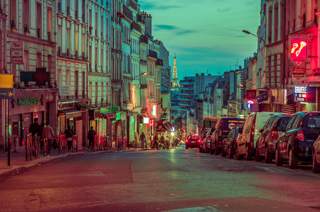 PARIS, FRANCE - JUNE 1, 2015: Beautiful and colorful evening parisian city street scene with Eiffel Tower in the background Editorial
