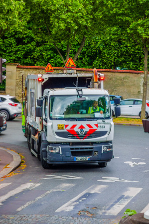 dumptruck: PARIS, FRANCE - JUNE 1, 2015: Garbage truck collecting garbagein the streets of downtown Paris