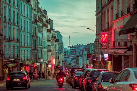 parisian scene: PARIS, FRANCE - JUNE 1, 2015: Beautiful evening parisian city street scene with Eiffel Tower in the background