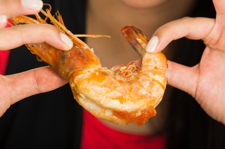 Close up shot of young woman eating a big shrimp with her hands Stockfoto