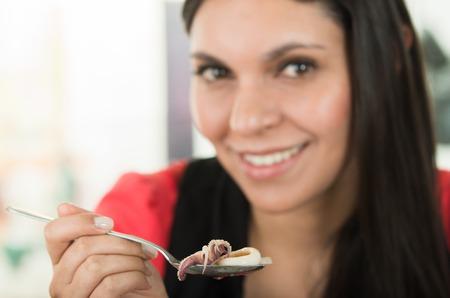 ecuadorian: Beautiful brunette girl eating fresh delicious calamari cebiche, typical ecuadorian plate, selective focus