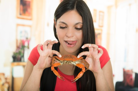 Beautiful young brunette latin girl enjoying a delicious crab. Close up shot