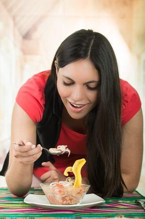 ecuadorian: Beautiful young happy brunette girl enjoying a delicious seafood cebiche, typical ecuadorian plate