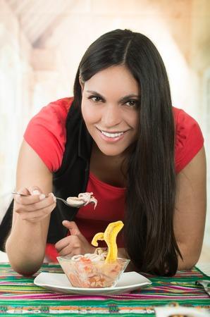ecuadorian: Beautiful young smiling brunette girl enjoying a delicious seafood cebiche, typical ecuadorian plate Stock Photo