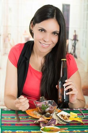 ecuadorian: Beautiful young happy brunette girl enjoying a delicious ecuadorian seafood cebiche with a cold beer