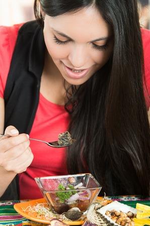 ecuadorian: Beautiful young brunette girl enjoying a delicious seafood cebiche, typical ecuadorian plate