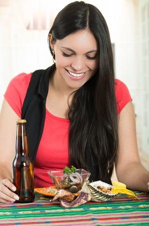 ecuadorian: Beautiful young brunette girl enjoying a beer and a delicious seafood cebiche, typical ecuadorian plate