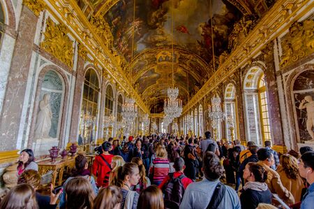 louis the rich heritage: Paris, France - June 1, 2015: Crowds of tourists visiting the impressive and beautiful Hall of Mirrors in Palace of Versailles.