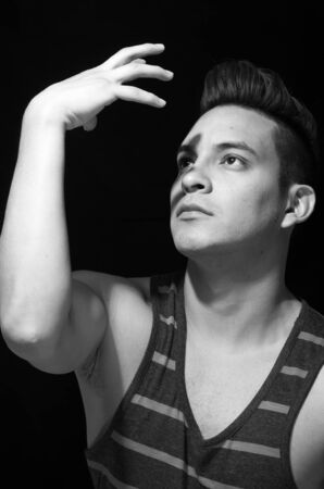 white singlet: Hispanic male wearing striped singlet, creating shadow upon face with own hands, black and white edition.