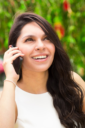 Classy attractive brunette wearing white dress talking on the phone in outdoors environment.