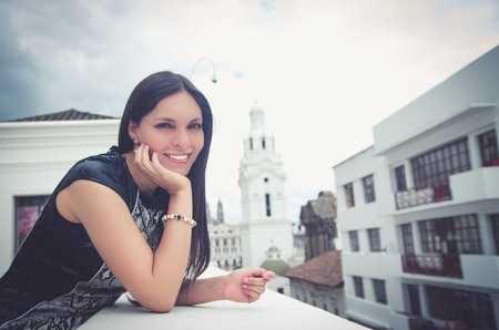Classy attractive brunette wearing black white dress in urban environment leaning on surface and enjoying a view while smiling.