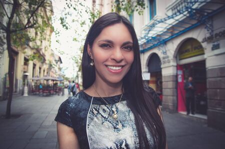 Classy attractive brunette wearing black white dress in city street looking into camera smiling.