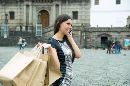 white dress: Classy attractive brunette wearing black white dress in urban environment carrying shopping bags and smiling.