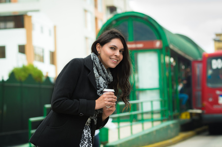 snobby: Brunette model wearing black jacket and grey scarf waiting for public transportation acting cold at station with cup of coffee .