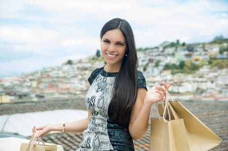 snobby: Classy attractive brunette wearing black white dress sitting on city rooftop with nice view holding shopping bags and smiling to camera.