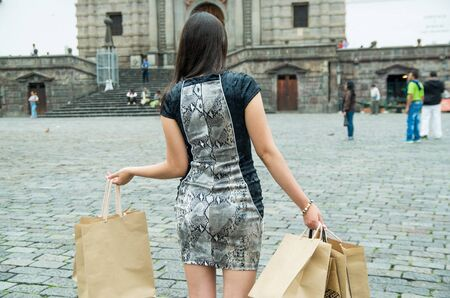 woman back: Brunette classy woman back facing camera walking across city plaza carrying shopping bags.