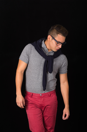 downwards: Hispanic male wearing tight shirt, sweater over shoulders, red pants and glasses portraying sophisticated hipster style, staring downwards, black background.