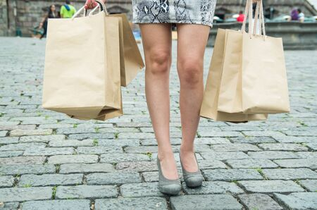 classy: Legs of classy woman wearing black white dress in urban plaza environment carrying shopping bags.