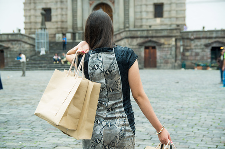 Brunette classy woman back facing camera walking across city plaza carrying shopping bags.