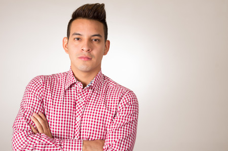 hispanic: Hispanic male wearing red white shirt posing smiling with arms crossed empty background.