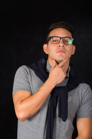facing to camera: Hispanic male wearing tight shirt, sweater over shoulders and glasses looking sophisticated facing camera, black background.