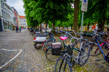bike parking: Bruges, Belgium - 11 August, 2015: Bike parking in city centre with bridge stoned road passing and green vegetation sorrounding. Editorial