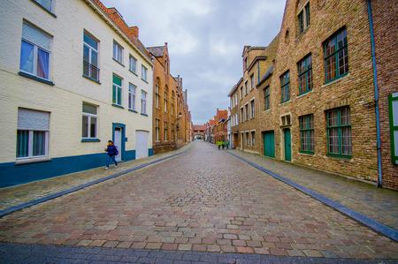 neighbourhood: Bruges, Belgium - 11 August, 2015: Very charming neighbourhood street with road covered by bridgestones and cute houses. Editorial