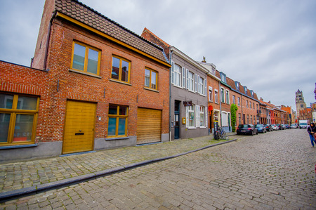 walloon: Bruges, Belgium - 11 August, 2015: Very charming neighbourhood street with road covered by bridgestones and cute houses. Editorial