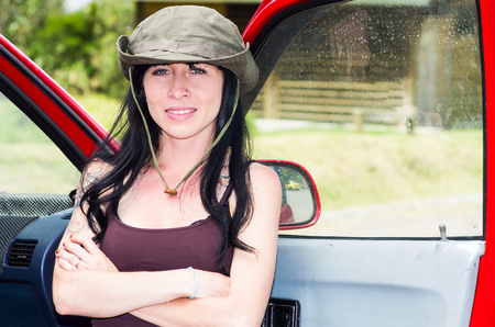 adventurous: Adventurous brunette wearing green safari hat, outdoors environment standing in red car door looking forward scouting.