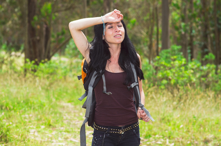 holding in arm: Adventurous brunette in hiking environment, facing camera holding arm against forehead tired, forest background.