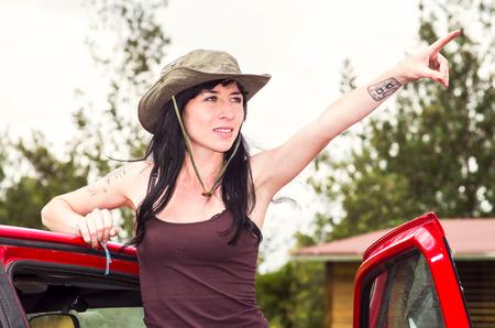 scouting: Adventurous brunette wearing green safari hat, outdoors environment standing in red car door looking forward scouting.
