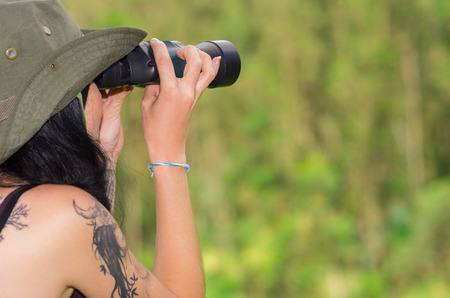 shot from behind: Brunette wearing green safari hat and tattoos on shoulder, holding up binoculars  looking forward, forest background, shot from behind angle. Stock Photo