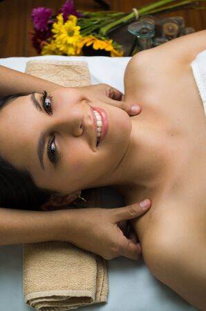 relaxation massage: Hispanic brunette model getting massage spa treatment, hands working on massaging womans shoulders with eyes open smiling.