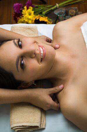 masajes relajacion: modelo morena hispana recibiendo tratamiento de spa masaje, manos trabajando en masajear los hombros womans sonriendo con los ojos abiertos.