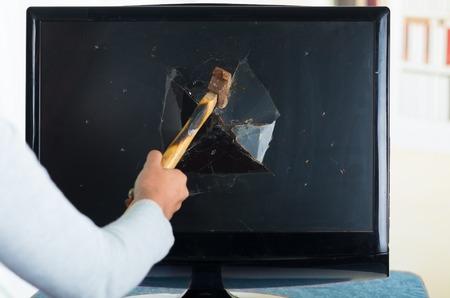 smashing: Female holding hammer smashing it into computer screen.